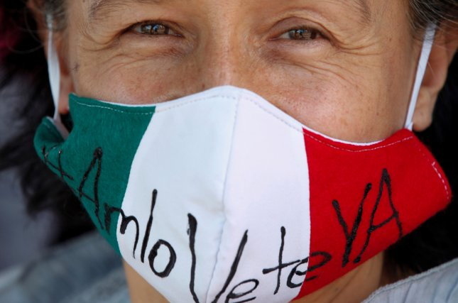 A man wears a facial mask adorned with the Mexican flag and a message that reads AMLO go away now -- in reference to Mexico's President Andres Manuel Lopez Obrador, during a protest in Guadalajara, Sunday. A vehicle caravan accuses the leader of having put the sovereignty, integrity and independence of the people of Mexico at risk, amid the coronavirus health contingency, organizers said. Photo by Francisco Guasco/EFE-EPA