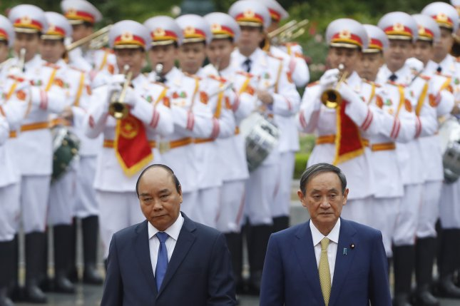 Japanese Prime Minister Yoshihide Suga (R) and his Vietnamese counterpart Nguyen Xuan Phuc (L) attend a welcoming ceremony at the Presidential Palace in Hanoi, Vietnam on Monday. Pool Photo by Kham/EPA-EFE