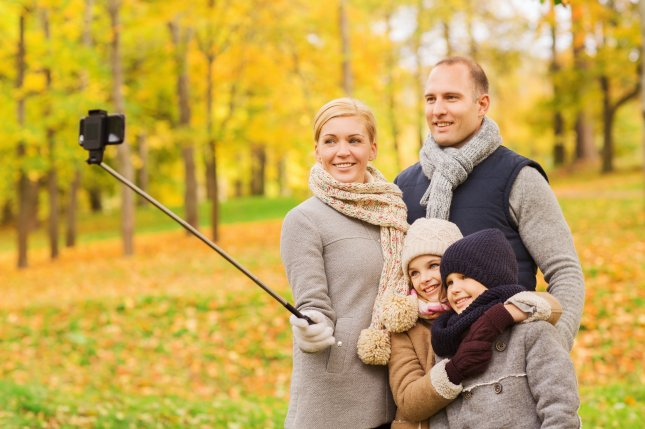 A family takes an outdoor portrait using a Bluetooth-enabled selfie stick. Photo by Syda Productions/Shutterstock