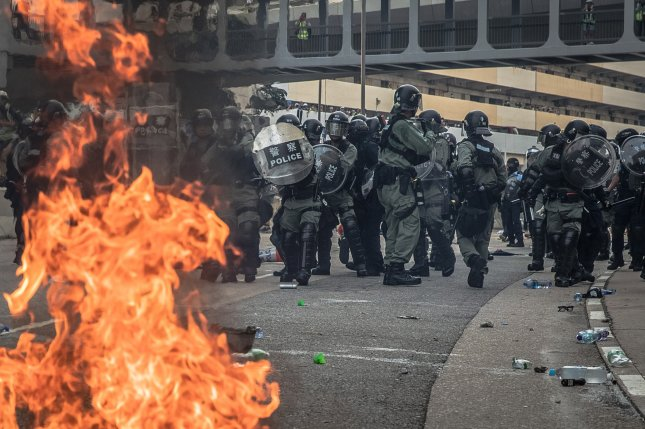 Riot police react after one of the protesters threw a bottle with flammable liquid during an anti-government march in Kwun Tong, Hong Kong on Saturday. Photo by Roman Pilipey/EPA-EFE