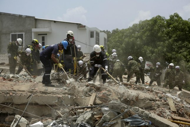 Colombian soldiers and rescue workers search for survivors at the site of a collapsed building in Cartagena on Friday after a six-story building collapsed on Thursday, killing 20 people and injuring 23. Photo by Ricardo Maldonado Rozo/EPA