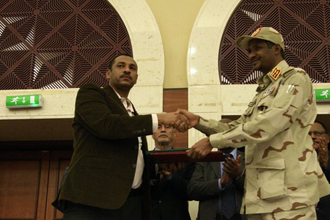 Deputy Chairman of the Transitional Military Council in Sudan Mohamed Hamdan Dagalo, also known as Hemedti, (R) and leader of the opposition movement Forces of Freedom and Change Ahmad al-Rabiah shake hands after signing a power-sharing agreement, in Khartoum, Sudan, on Wednesday. EPA-EFE/STRINGER
