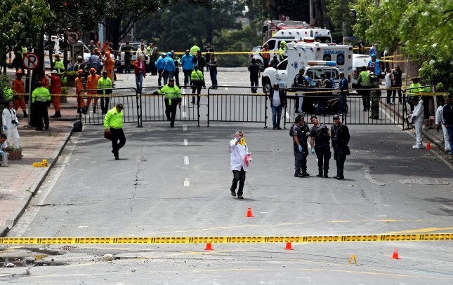Crime scene investigators of the Colombian Police examine the area of an explosion in the La Macarena neighborhood of Bogota, Colombia, on Sunday. At least 31 people, many of them police officers, were injured by the explosion. Police presence was high in the area as the last run of the bullfighting season in the Colombian capital was scheduled to be held at the bullring, La Santamaria. Photo by Leonardo Munoz/EPA