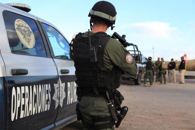 Agents of the Rural Tactical Operations Forces search for people responsible for an attack on a family in Bavispe, Mexico, Tuesday. One suspect has been arrested. Photo by Luis Torres/EPA-EFE
