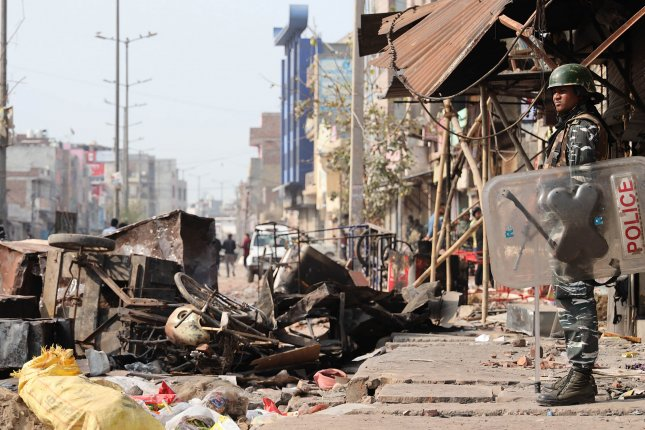 A riot police officer stands among debris at a damaged area in East Delhi that was affected by deadly clashes in Delhi on Thursday. Photo by EPA-EFE