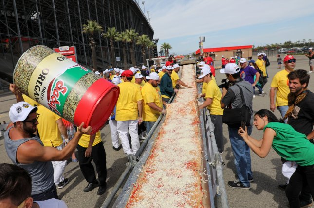 Pizza makers and hundreds of volunteers gathered in Fontana, Calif. to claim the Guinness World Record for the world's longest pizza, which measured 6,330 feet long. Photo by Eugene Garcia/EPA