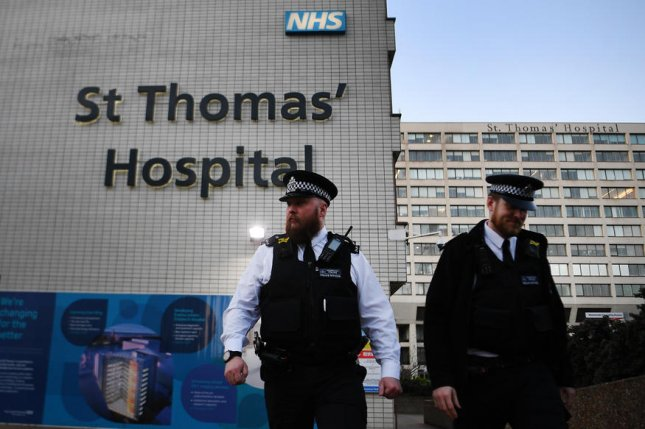 Police stand guard outside St. Thomas' Hospital in London on Tuesday, where British Prime Minister Boris Johnson spent the night in intensive care. Photo by Andy Rain/EPA-EFE
