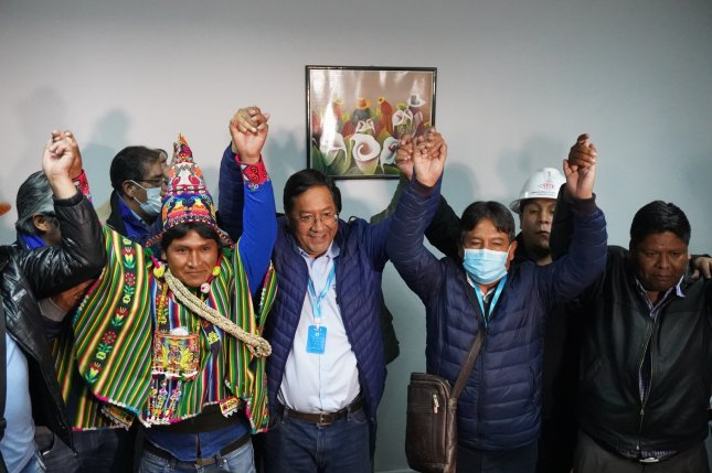 Luis Arce (C) and vice presidential candidate David Choquehuanca (3-R) celebrate on Monday after seeing unofficial results that indicate they received more than 50% of the vote, in La Paz, Bolivia. Photo by EPA-EFE