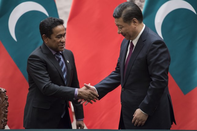 Former Maldives President Abdulla Yameen shakes the hand of Chinese President Xi Jinping. Yameen lost re-election in September and now faces money laundering charges. File Photo by Fred Dufour/EPA-EFE