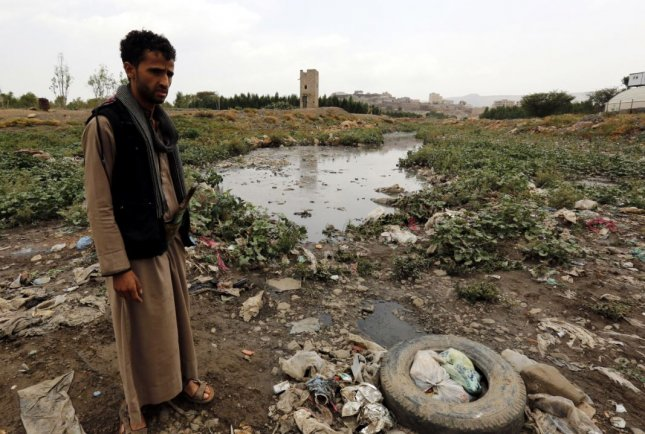 A Yemeni stands near a sewage swamp covered with plastic waste and creating a high-risk environment for cholera, in Sana'a, Yemen, 26 July 2017. British charity Oxfam warned the cholera outbreak, which has reached 745,205 suspected cases, could soon become the largest in recorded history. File photo Yahya Arhab/EPA/Y