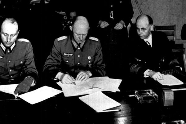 Germany's Gen. Gustav Jodl (C) signs the unconditional surrender documents on May 7, 1945, in Reims, France, ending the war in Europe. He is flanked by Col. Wilhelm Oxenius (L), his aide, and German Adm. Hans Georg von Friedeburg. UPI File Photo