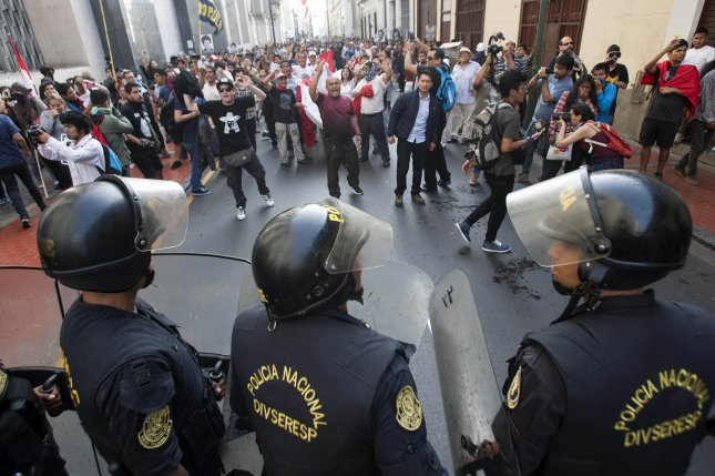 Riot police officers block passage of protesters during a demonstration against the pardon to ex-president Alberto Fujimori, in Lima, Peru on Monday. Photo by Eduardo Cavero/EPA-EFE