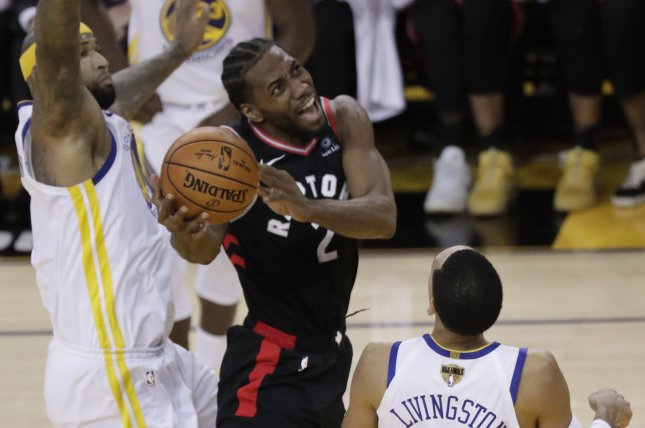 Toronto Raptors forward Kawhi Leonard (2) goes to the basket against Golden State Warriors defenders DeMarcus Cousins (L) and Shaun Livingston (R) during the second half in Game 3 of the NBA Finals on Wednesday night at Oracle Arena in Oakland, California. Photo by Monica Davey/EPA-EFE