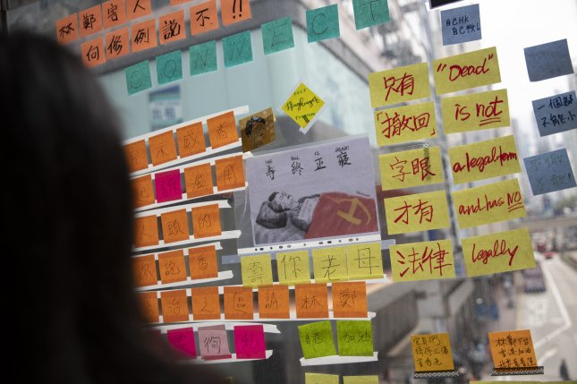 People look at messages pasted on a Lennon Wall on a pedestrian bridge on Wan Chai district in Hong Kong on Thursday. The sites have become lightning rods for protests and fights. Photo by How Hwee Young/EPA-EFE/