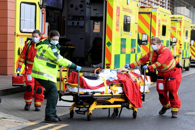 Ambulance workers assist a patient outside the Royal London Hospital in London, Britain, on Sunday. It was one of many ambulances lined up at the hospital as hospitalizations for coronavirus surge. Photo by Facundo Arrizabalaga/EPA-EFE