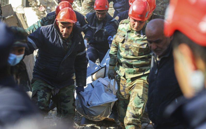 Azerbaijan rescuers carry a body of a local resident killed by shelling in Ganja, Azerbaijan, on Oct. 11. Photo by Aziz Karimov/EPA-EFE