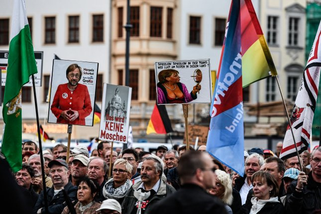 Supporters of the Pegida movement and German right-wing populist party Alternative for Germany hold banners against German Chancellor Angela Merkel during a demonstration in front of the Frauenkirche church at Neumarkt square in Dresden, Germany, on September 17, 2017. Photo by Filip Singer/EPA-EFE