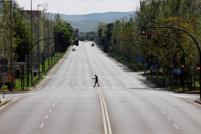 A stroller crosses a deserted road in Cordoba, Andalusia, Spain, on Sunday. Photo by EPA-EFE/Salas