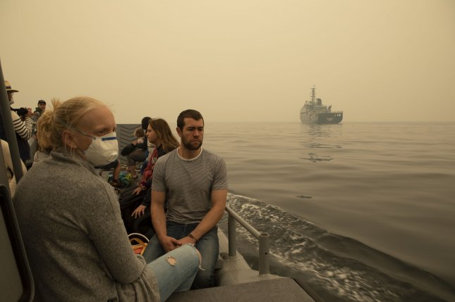 Evacuees from Mallacoota are transported on a landing craft to a ship at sea on Friday during bushfire relief efforts. Photo coutesy of LSIS Shane Cameron/Royal Australian Navy/EPA-EFE
