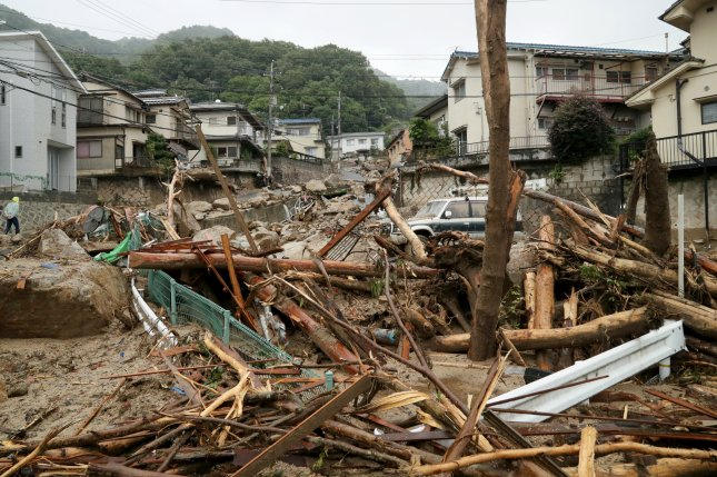 Flooding by heavy rain damages a residential district in Hiroshima, Hiroshima Prefecture on Sunday. At least 76 people have died in the flooding in central and western Japan and more than 1.6 million people have been ordered to evacuate from their homes. Photo by JiJI Press/EPA
