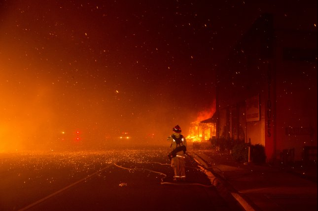 A firefighter watches as the Camp Fire burns Thursday in Paradise, Calif. The blaze has torched tens of thousands of acres. Photo by Peter Dasilva/EPA-EFE