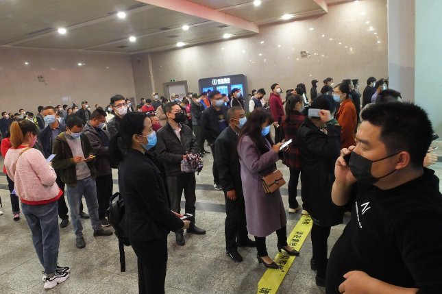 Travelers line up to buy train tickets at a railway station in Yichang, Hubei province, China, on Wednesday. Chinese authorities have lifted travel restrictions for residents of Hubei Province. Photo by Liu Junfeng/EPA-EFE