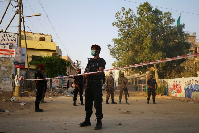 Pakistani security officials stand guard Saturday, a day after a passenger plane of state run Pakistan International Airlines crashed in a residential area, in Karachi, Pakistan. Photo by Shahzaib Akber/EPA-EFE
