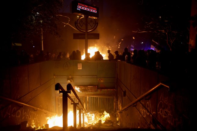 Demonstrators stand near fires during a protest against the government of President Sebastian Pinera in the streets of Santiago, Chile, on Monday. Photo by Fernando Bizerra Jr./EPA-EFE
