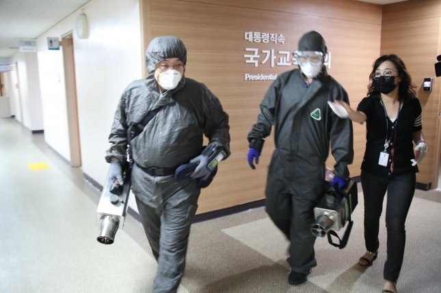 Quarantine officials enter the government complex in Seoul on Friday as the family members of an official working on the third floor of the building tested positive for COVID-19. Photo courtesy of Yonhap/EPA-EFE