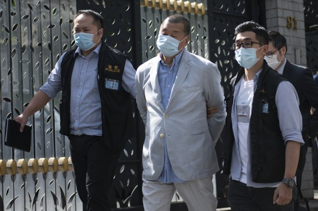 Jimmy Lai (C), media tycoon and founder of Apple Daily, is escorted by police after he was arrested at his home in Hong Kong on Monday. Photo by Vernon Yuen/EPA-EFE