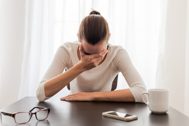 A businesswoman who does not appear to be feeling well. Photo by KieferPix/Shutterstock