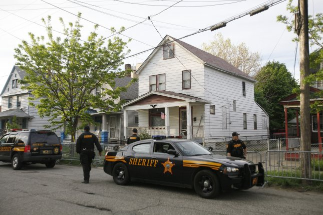 Officers stand watch in front of the house of kidnapper Ariel Castro on Seymour Avenue in Cleveland, Ohio, May 7, 2013, one day after Amanda Berry, Gina DeJesus and Michelle Knight were rescued after years of captivity. Note the broken front screen door, through which one of the girls was pulled to safety by a neighbor. File Photo by David Maxwell/EPA-EFE