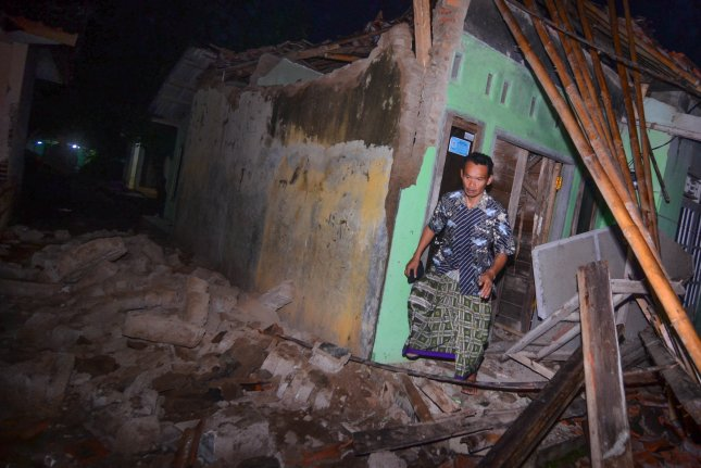 An Indonesian man walks out of a damaged house as he checks on his belongings after the 6.5-magnitude earthquake hit Tasikmalaya, West Java, Indonesia, on Friday. Photo by STR/EPA-EFE
