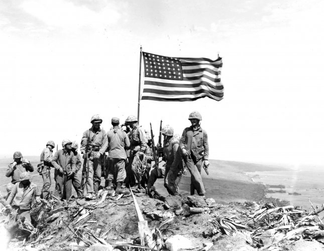 In the stiff breeze atop Iwo Jima's Mount Suribachi, Old Glory whips against the sky as members of the 5th Marine Division raise their voices and weapons in celebration, capturing the moment for posterity on February 23, 1945. File Photo by Pvt. Bob Campbell/USMC/UPI
