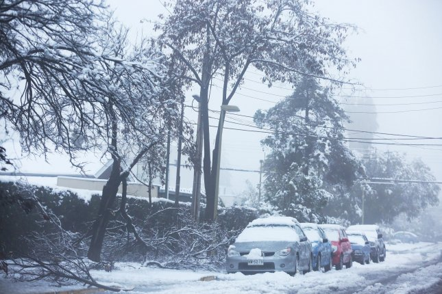 Vehicles on a street in Chile's capital of Santiago were covered in snow on Saturday due to a rare snowfall. Photo by Elvis Gonzalez/EPA