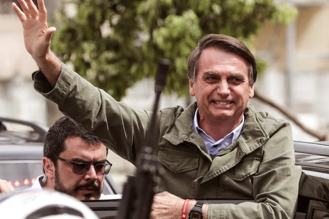 New Brazilian president Jair Bolsonaro (R) of the Social Liberal Party (PSL) waves to supporters after voting at a polling station in Rio de Janeiro, Brazil Oct. 28. Photo by Antonio Lacerda/EPA