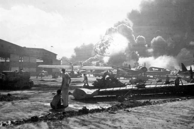 Sailors stand amid wrecked planes at the Ford Island seaplane base, watching as USS Shaw explodes in the center background December 7 1941. USS Nevada is also visible in the middle background, with her bow headed toward the left. File Photo by U.S. Navy/UPI