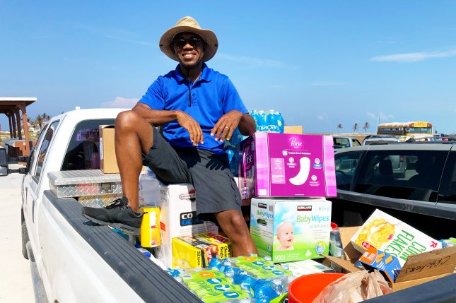 Brian Seymour of Grand Bahama Island sits on a generator and a truckload of donated food, buckets, and tools Saturday at Old Bahama Bay Resort in the island's West End community. Photo by Paul Brinkmann/UPI
