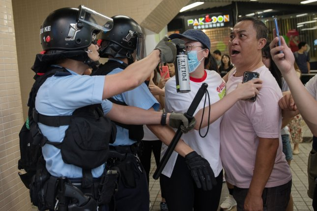 A police officer points a can of pepper spray at a local resident in Amoy Plaza in Hong Kong, China, Saturday. Shopping malls have become the latest hot spots in the city as large numbers of pro-China supporters and anti-government protesters come to blows as they try to out-sing and out-shout each other. Photo by Jerome Favre/EPA-EFE