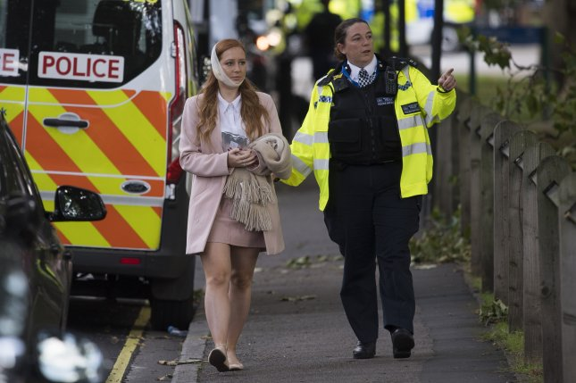 An injured woman is escorted away from 'Parsons Green' station in London on Friday after a terrorist device detonated during the morning rush hour. Photo by Matt Oliver/EPA