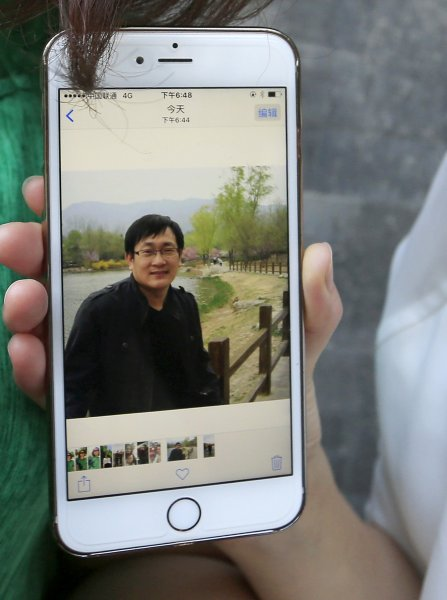 Li Wenzu (out of frame) holds up a mobile phone showing a photo of her husband, human rights lawyer Wang Quanzhang, who was arrested in July 2015, in Beijing, China. Photo by How Hwee Young/EPA-EFE