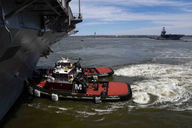 Tug boats ferry the Nimitz-class aircraft carrier USS Harry S. Truman from Naval Station Norfolk following a three-month availability period used to upgrade systems, conduct maintenance, and provide targeted training. Photo by Mass Communication Specialist 3rd Class Maxwell Higgins/U.S. Navy