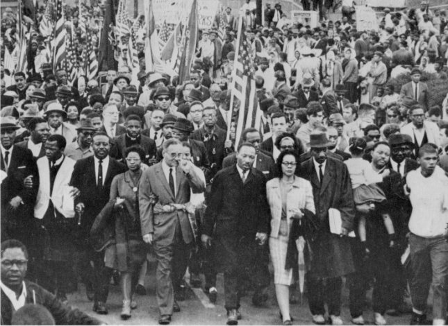 Dr. Martin Luther King leads an estimated 10,000 or more civil-rights marchers out on the last leg of their Selma-to-Montgomery march on March 25, 1965. UPI File Photo