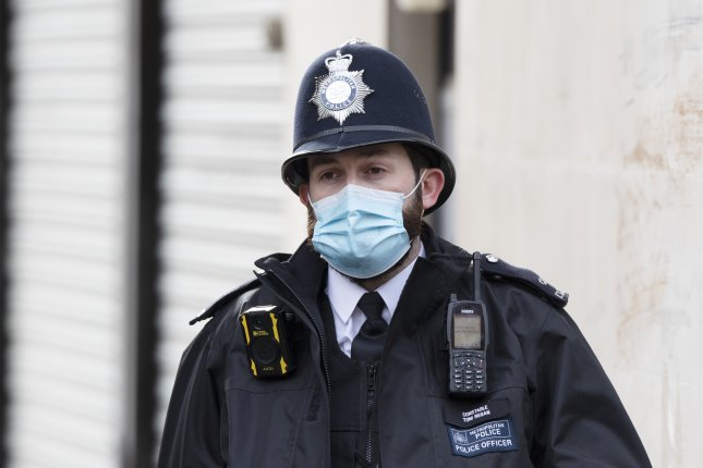 A police officer in a mask outside King Edward VII hospital in London on Saturday. Britain's Prince Philip, is continuing recovering in the hospital after having a successful operation on his heart. Photo by Arrizabalaga/EPA-EFE