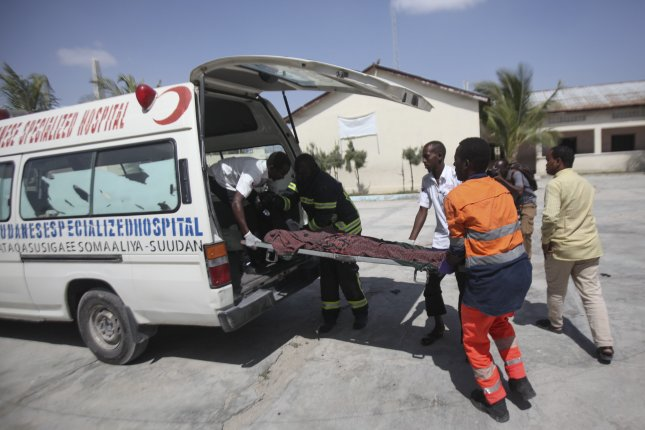 A victim is carried into an ambulance at the scene of twin explosions Saturday in Mogadishu. Photo by Said Yusuf Warsame/EPA-EFE
