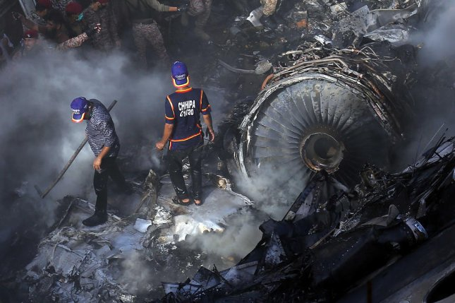 Crews search the debris of a Pakistan International Airlines jetliner after it crashed in Karachi, Pakistan, on May 22. An early investigative report Wednesday faulted both the pilots and ground controllers. File Photo by Shahzaib Akber/EPA-EFE