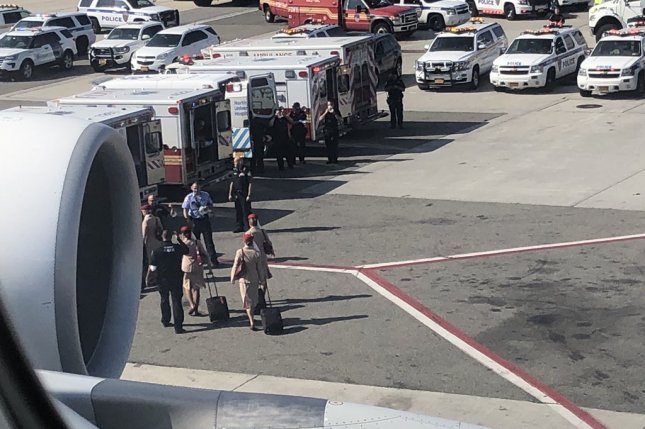 A photo taken by a passenger aboard Emirates Flight 203 shows flight crew members and ambulances at John F. Kennedy Airport in New York City Wednesday. The plane was quarantined for a time due to symptoms of illness in several passengers. Photo by Larry Cohen/EPA-EFE