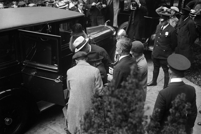 Albert B. Fall, former secretary of interior, is helped into his car as he leaves the District and Supreme Court in Washington, D.C., on October 25, 1929. Fall was found guilty of accepting a bribe of $100,000 from E.L. Doheny as part of the Teapot Dome Scandal. File Photo by Library of Congress/UPI