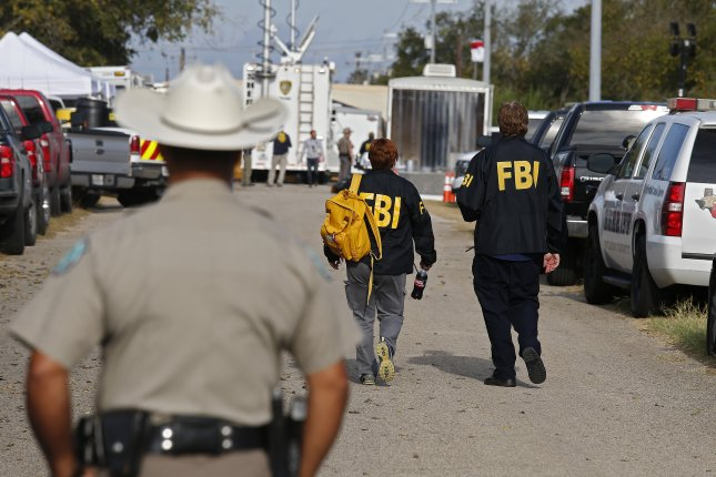 A Texas state trooper watches as two FBI investigators walk toward the First Baptist Church in Sutherland Springs, Texas, on Monday. Photo by Larry W. Smith/EPA-EFE