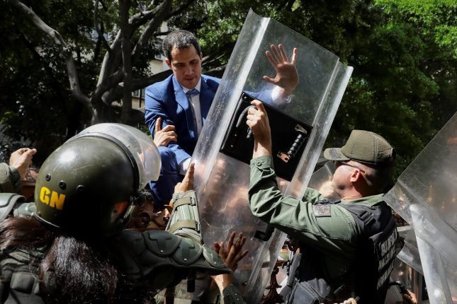 Venezuelan opposition leader Juan Guaido climbs a fence in an attempt to enter the headquarters of the National Assembly as security forces prevented him from entering the National Assembly headquarters for a vote on whether to reelect him as the head of the parliamentary body. Photo by Rayner Pena/EPA-EFE